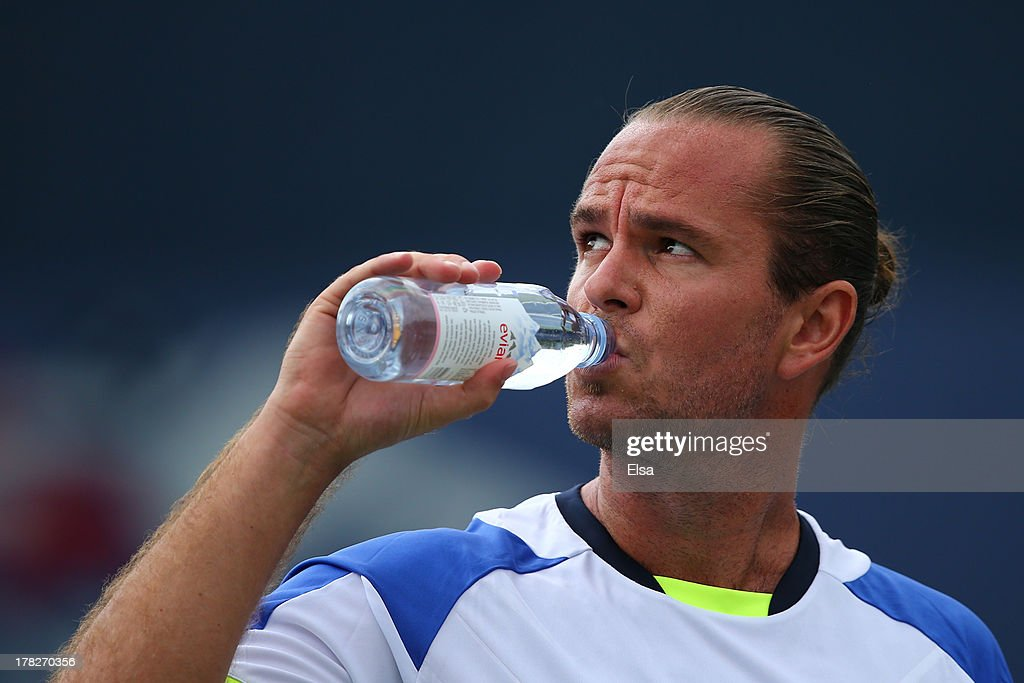 Xavier Malisse of Belgium drinks during a break in his men's singles first round match against Andreas Seppi of Italy on Day Three of the 2013 US Open at USTA Billie Jean King National Tennis Center on August 28, 2013 in the Flushing neighborhood of the Queens borough of New York City.