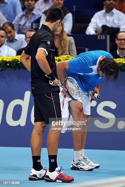 Xavier Malisse of Belgium looks at his injured leg as Novak Djokovic of Serbia looks on during day two of the Swiss Indoors at St Jakobshalle on...