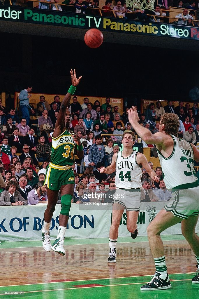 Xavier McDaniel #34 of the Seattle Supersonics passes against Larry Bird #33 and Danny Ainge #44 of the Boston Celtics during a game played in 1987 at the Boston Garden in Boston, Massachusetts.