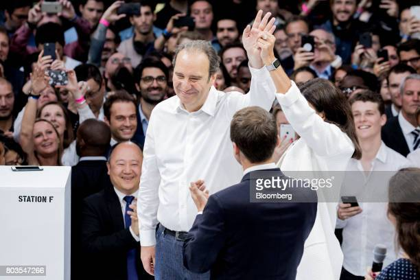 Xavier Niel billionaire and cochief operating officer of Iliad SA left is applauded by attendees on stage with Emmanuel Macron France's president and...