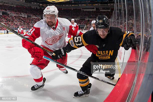 Xavier Ouellet of the Detroit Red Wings battles along the boards with Ryan Spooner of the Boston Bruins during an NHL game at Joe Louis Arena on...
