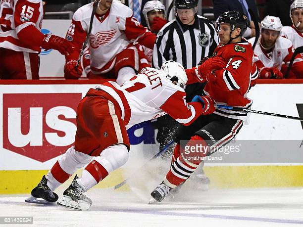 Xavier Ouellet of the Detroit Red Wings hits Richard Panik of the Chicago Blackhawks at the United Center on January 10 2017 in Chicago Illinois The...