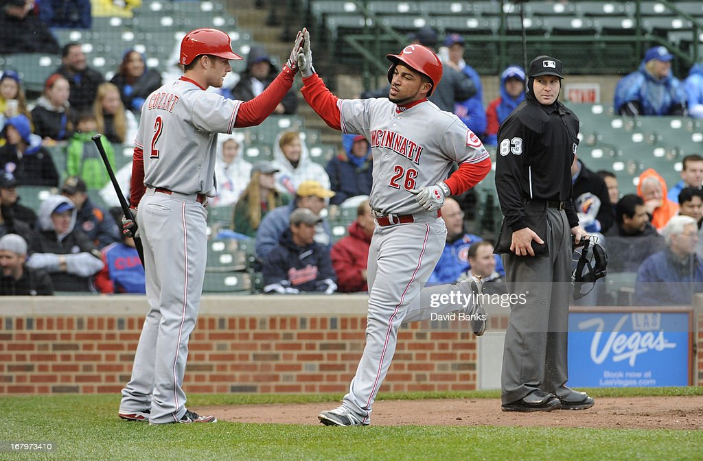 Xavier Paul #26 of the Cincinnati Reds is greeted by Zack Cozart #2 of the Cincinnati Reds after scoring against the Chicago Cubs during the second inning on May 3, 2013 at Wrigley Field in Chicago, Illinois.