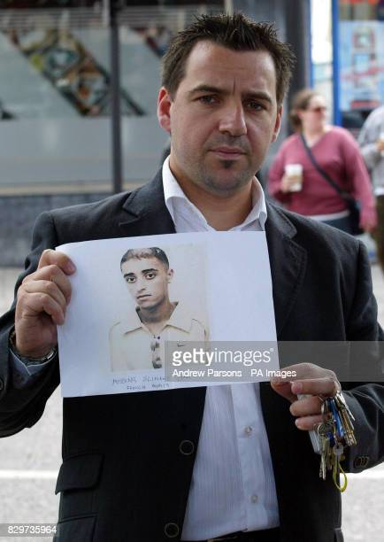 Xavier Rebergue with a picture of his friend Slimane Ihab who has been missing since yesterday's bomb blasts in London
