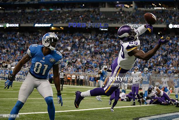 Xavier Rhodes of the Minnesota Vikings tries to pull in a fourth quarter interception next to Calvin Johnson of the Detroit Lions at Ford Field on...