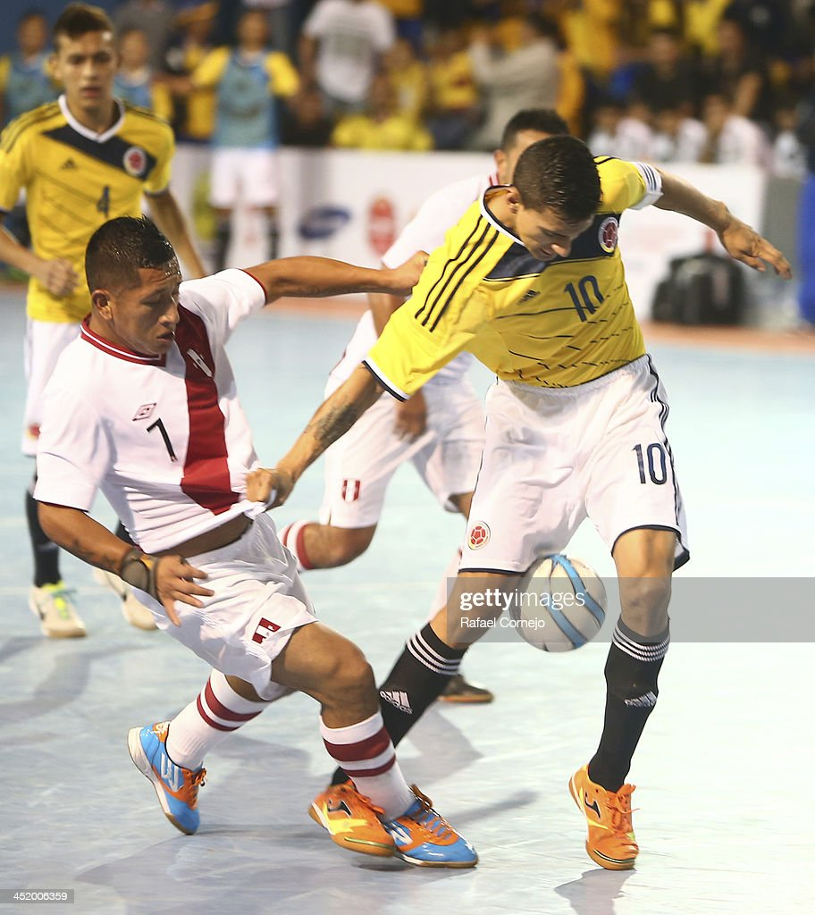 Xavier Tavera of Colombia fights for the ball with Luis Salerno of Peru during a match between Colombia and Peru as part of the XVII Bolivarian Games Trujillo 2013 at Videna San Luis on November 25, 2013 in Lima, Peru.