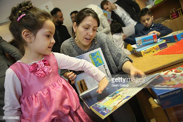 Xenia and her mother both from Moldova page through a book in German about animals during the presentation of a new initiative to help children of...