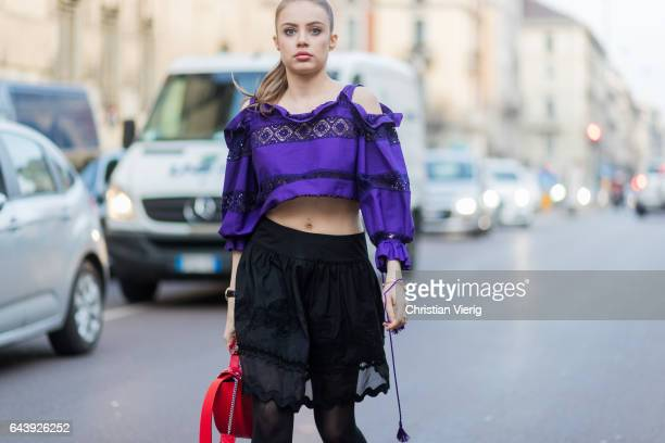 Xenia Tchoumitcheva wearing a purple cropped top black mini skirt tights outside Alberta Ferretti on February 22 2017 in Milan Italy