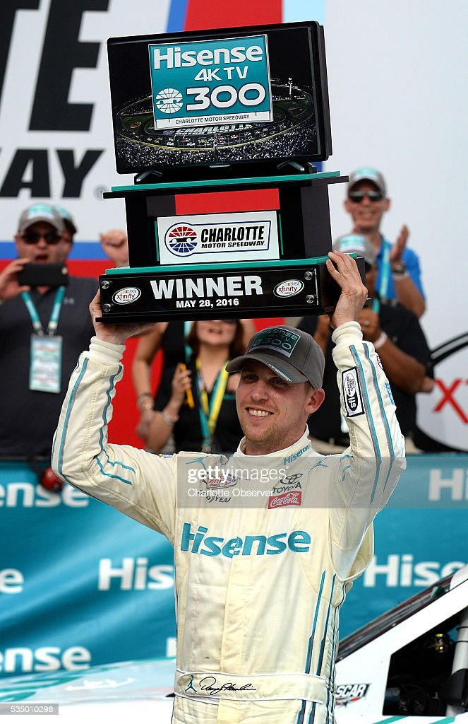 Xfinity Series driver Denny Hamlin smiles as he hoists the trophy for winning the 35th Annual Hisense 300 at Charlotte Motor Speedway in Concord, N.C., on Saturday, May 28, 2016.