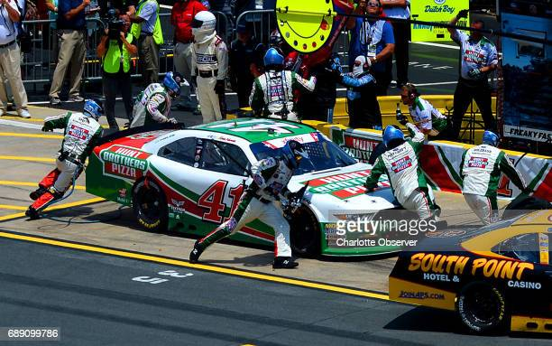 Xfinity Series driver Kevin Harvick's pit crew rushes around the car to make adjustments during the Hisense 4K TV 300 at Charlotte Motor Speedway in...