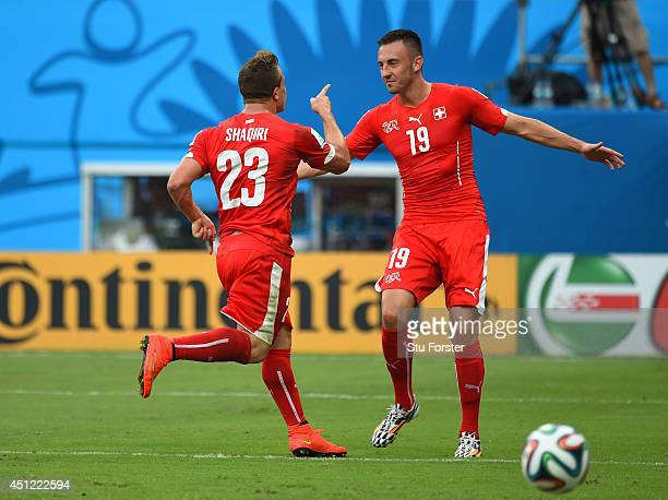 Xherdan Shaqiri celebrates scoring his team's second goal with Josip Drmic of Switzerland during the 2014 FIFA World Cup Brazil Group E match between...