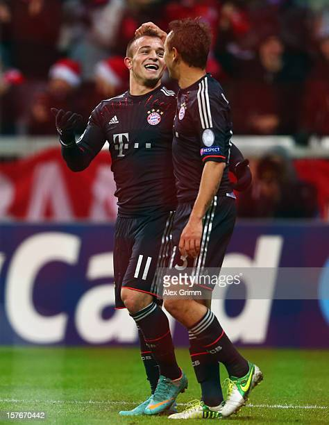 Xherdan Shaqiri of Muenchen celebrates his team's third goal with team mate Rafinha during the UEFA Champions League Group F match between FC Bayern...
