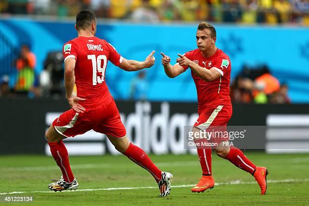 Xherdan Shaqiri of Switzerland celebrates scoring his team's second goal with his teammate Josip Drmic during the 2014 FIFA World Cup Brazil Group E...