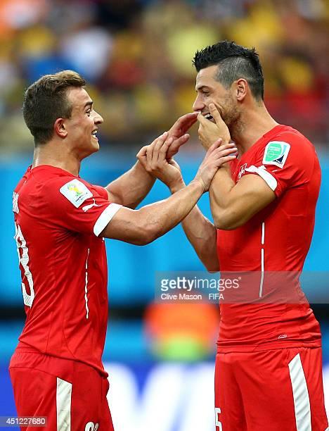 Xherdan Shaqiri of Switzerland speaks to Blerim Dzemaili as he is replaced during the 2014 FIFA World Cup Brazil Group E match between Honduras and...