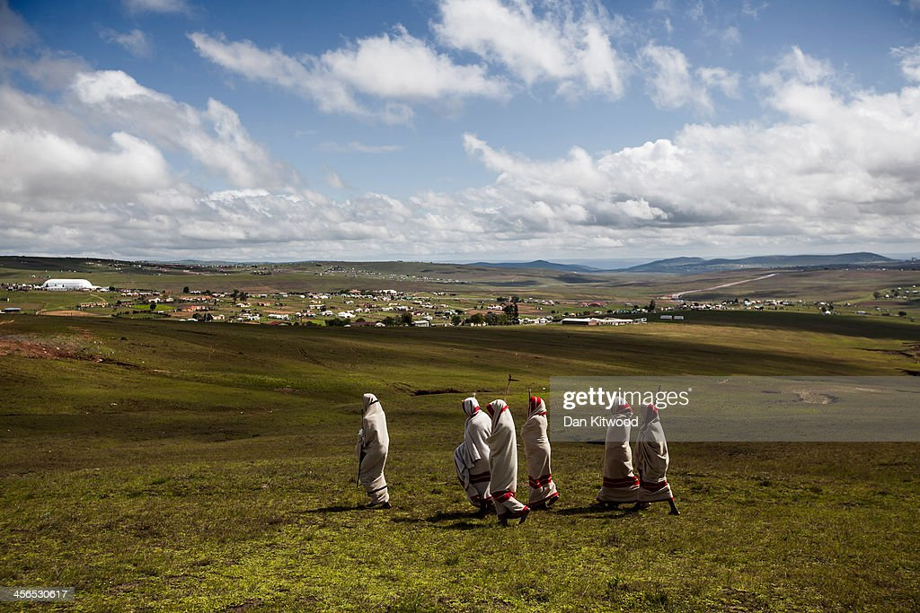 Xhosa youths walk over a hillside overlooking the home town of former South African President Nelson Mandela before his funeral cortege arrives at his family's home on December 14, 2013 in Qunu, South Africa. Mandela's body will remain in his home town of Qunu, Eastern Cape, overnight and be buried Sunday. Mr. Mandela passed away on the evening of December 5, 2013 at his home in Houghton at the age of 95. Mandela became South Africa's first black president in 1994 after spending 27 years in jail for his activism against apartheid in a racially-divided South Africa.