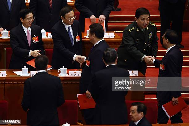 Xi Jinping China's president center and Li Keqiang China's premier right shake hands with delegates as they leave the closing session of the third...