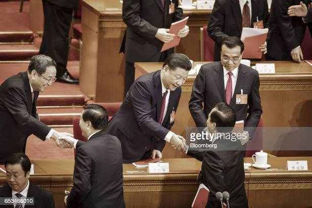 Xi Jinping China's president center and Yu Zhengsheng chairman of the Chinese People's Political Consultative Conference left shake hands with...