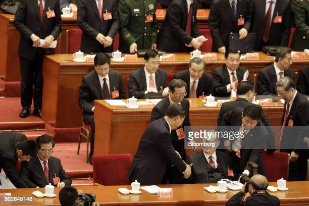 Xi Jinping China's president center shakes hands with Jiang Zemin China's former president after delivering his speech at the opening of the 19th...