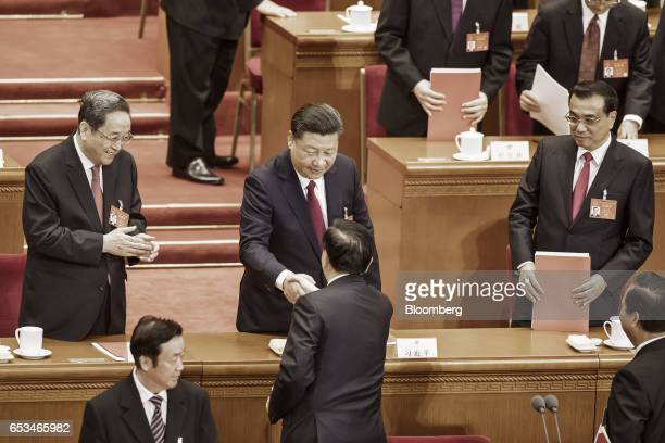 Xi Jinping China's president center shakes hands with members of the Politburo as Li Keqiang China's premier right and and Yu Zhengsheng chairman of...