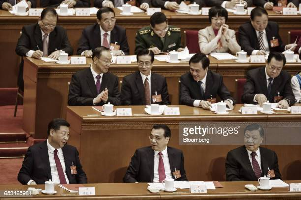 Xi Jinping China's president front row left to right speaks to Li Keqiang China's premier as Liu Yunshan deputy general secretary of the Communist...