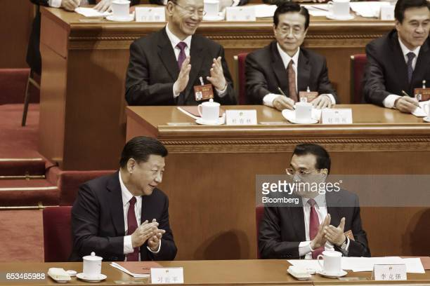 Xi Jinping China's president left speaks with Li Keqiang China's premier right during the closing ceremony of the National People's Congress in...