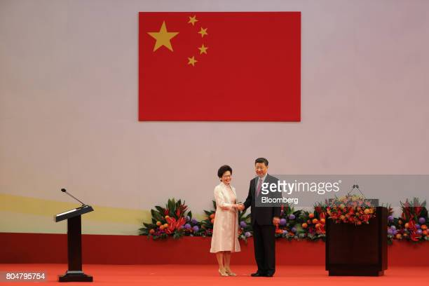 Xi Jinping China's president right shakes hands with Carrie Lam Hong Kong's incoming chief executive after she recites her oath of office during a...