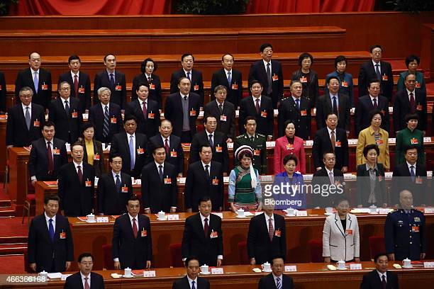 Xi Jinping China's president second row left Li Keqiang China's premier second row second left and other delegates stand singing the national anthem...
