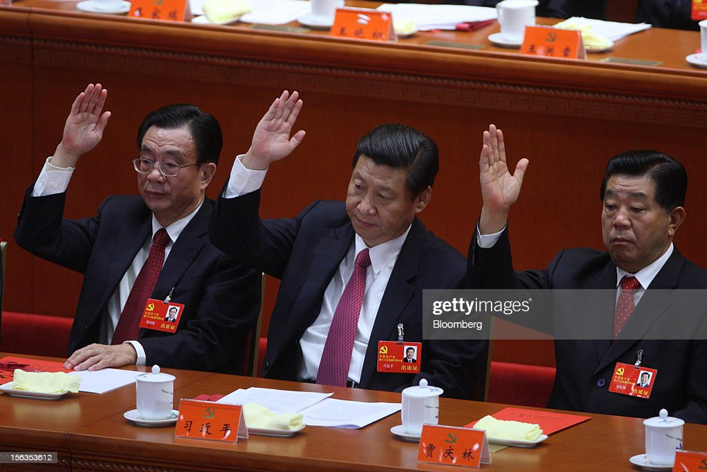 Xi Jinping, China's vice president, center, raises his hand during the closing session of the 18th National Congress of the Communist Party of China at the Great Hall of the People in Beijing, China, on Wednesday, Nov. 14, 2012. Xi and Vice Premier Li Keqiang were reappointed to the Chinese Communist Party's Central Committee, positioning them to take over the top two posts in the world's second-biggest economy. Photographer: Tomohiro Ohsumi/Bloomberg via Getty Images