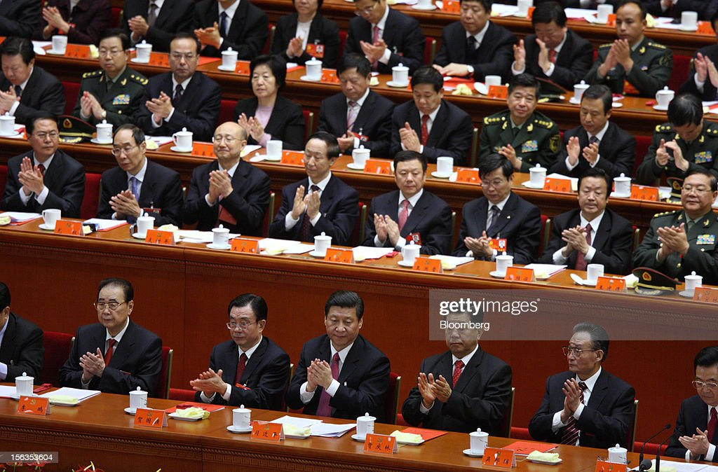 Xi Jinping, China's vice president, front row center, and Hu Jintao, president, front row right, clap during the closing session of the 18th National Congress of the Communist Party of China at the Great Hall of the People in Beijing, China, on Wednesday, Nov. 14, 2012. Xi and Vice Premier Li Keqiang were reappointed to the Chinese Communist Party's Central Committee, positioning them to take over the top two posts in the world's second-biggest economy. Photographer: Tomohiro Ohsumi/Bloomberg via Getty Images