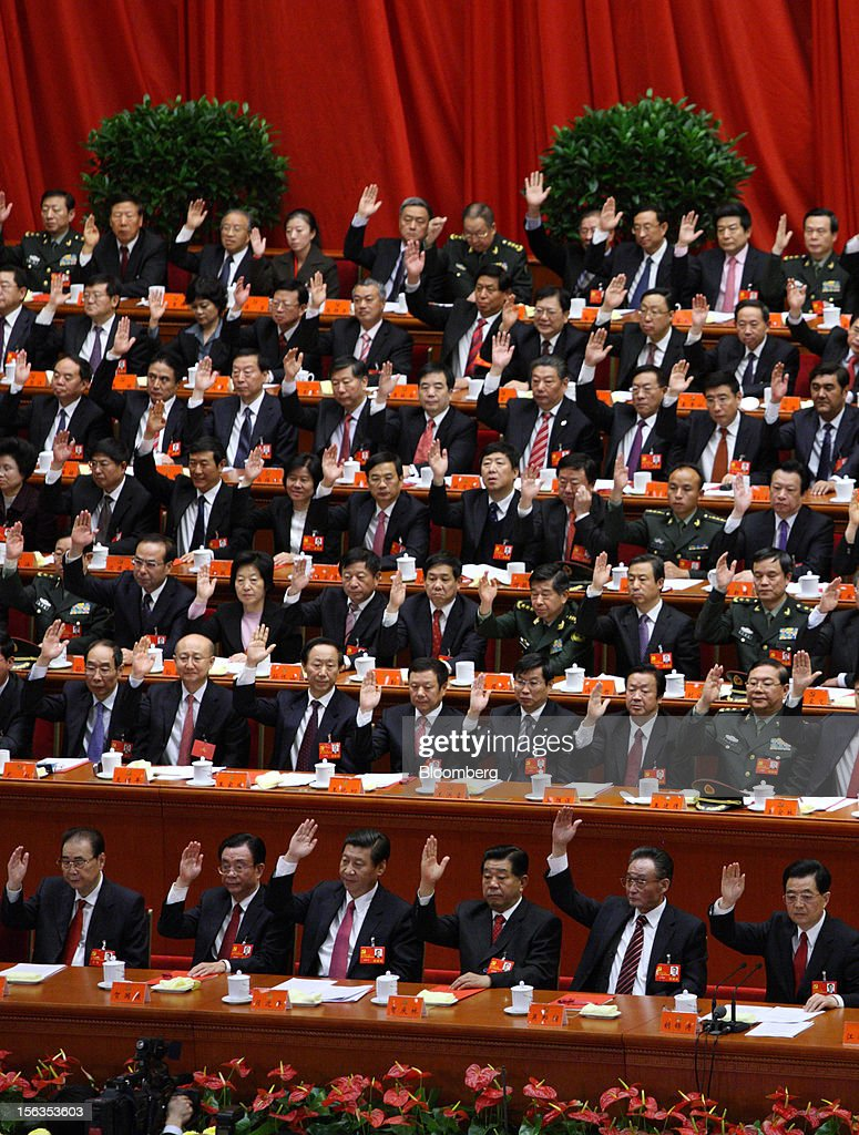 Xi Jinping, China's vice president, front row third left, and Hu Jintao, president, front row right, raise their hands during the closing session of the 18th National Congress of the Communist Party of China at the Great Hall of the People in Beijing, China, on Wednesday, Nov. 14, 2012. Xi and Vice Premier Li Keqiang were reappointed to the Chinese Communist Party's Central Committee, positioning them to take over the top two posts in the world's second-biggest economy. Photographer: Tomohiro Ohsumi/Bloomberg via Getty Images