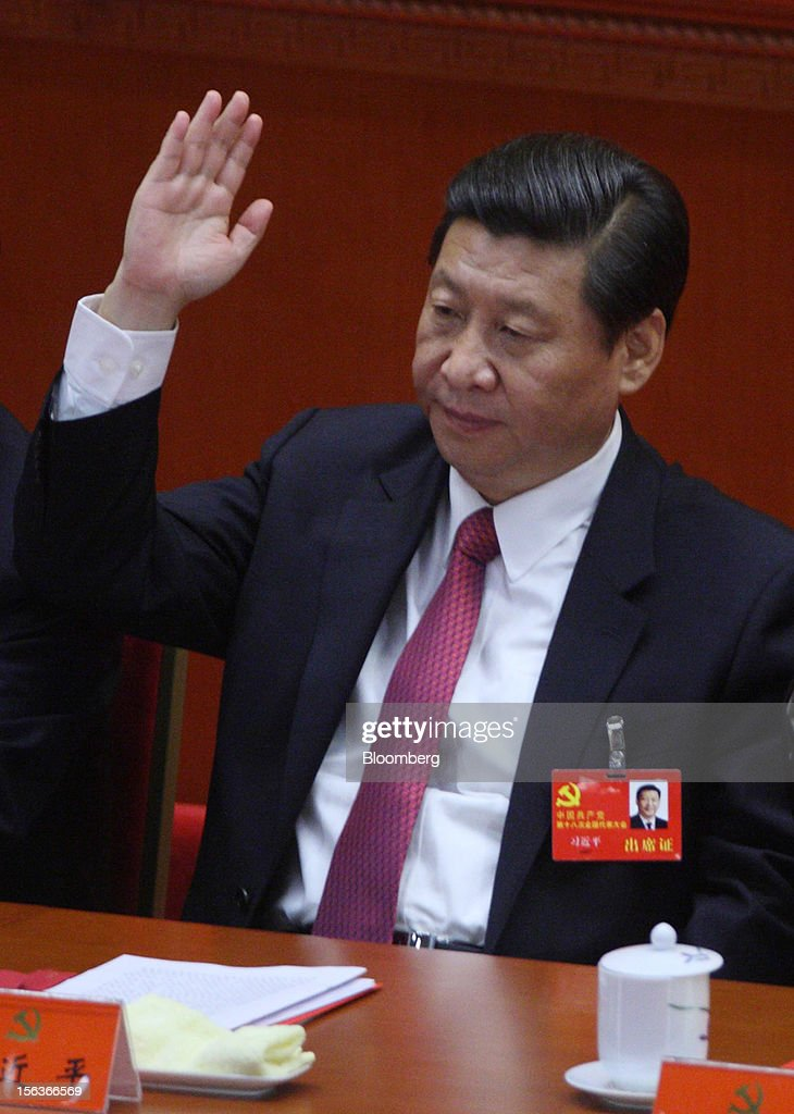 Xi Jinping, China's vice president, raises his hand during the closing session of the 18th National Congress of the Communist Party of China at the Great Hall of the People in Beijing, China, on Wednesday, Nov. 14, 2012. Xi and Vice Premier Li Keqiang were reappointed to the Chinese Communist Party's Central Committee, positioning them to take over the top two posts in the world's second-biggest economy. Photographer: Tomohiro Ohsumi/Bloomberg via Getty Images