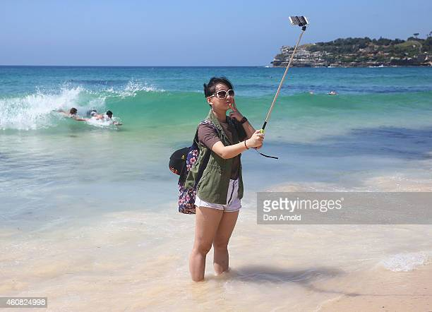 Xia Yao from Shanghai China takes a photo on her selfie stick at Bondi Beach on December 25 2014 in Sydney Australia Bondi Beach is a popular tourist...