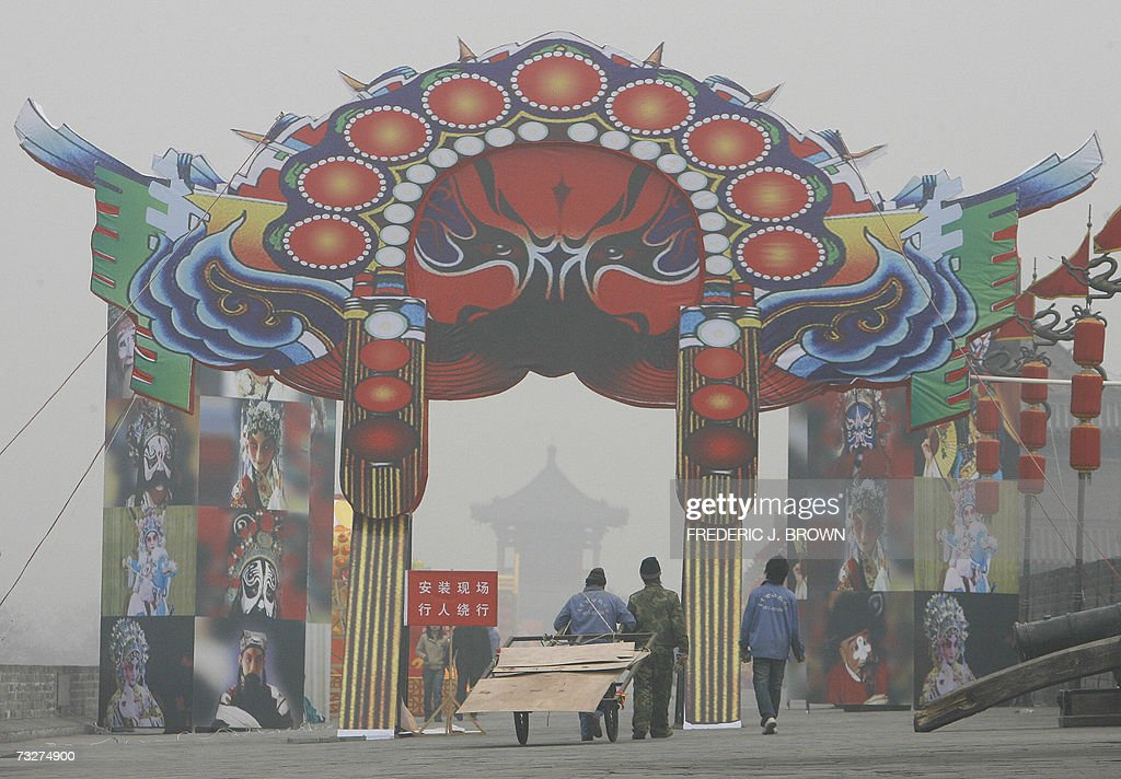Workers walk through an archway on a polluted day depicting Shaanxi Opera set up for Lunar New Year festivities along the south gate city wall 08...