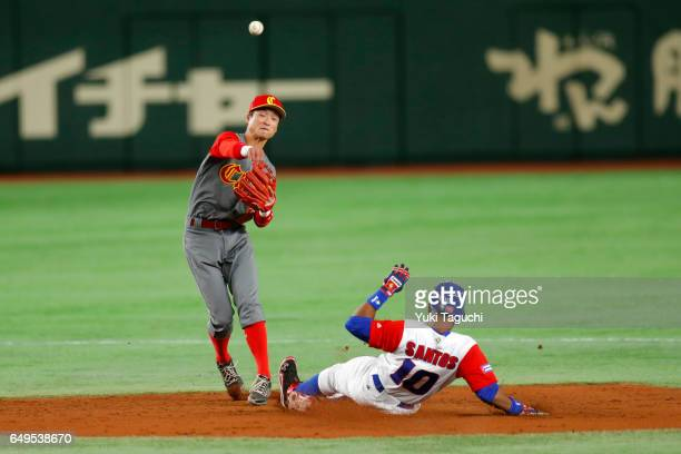 Xiaolei Du of Team China turns a double play as Roel Santos of Team Cuba slides into second base in third inning during Game 2 of Pool B at the Tokyo...
