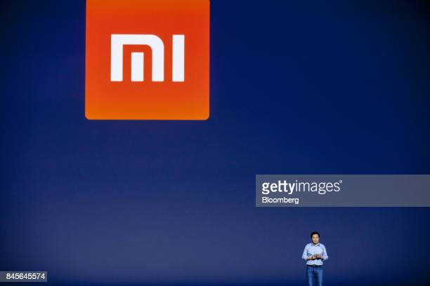 A Xiaomi Corp logo sits on a screen as Lei Jun billionaire and chief executive officer of Xiaomi Corp speaks during the launch of the company's Mi...