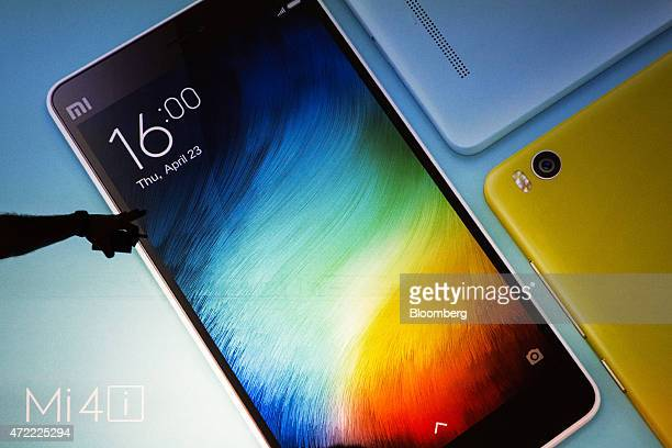 Xiaomi Corp Mi 4i smartphones are displayed on a screen during a news conference in Hong Kong China on Tuesday May 5 2015 The Mi 4i which runs on...