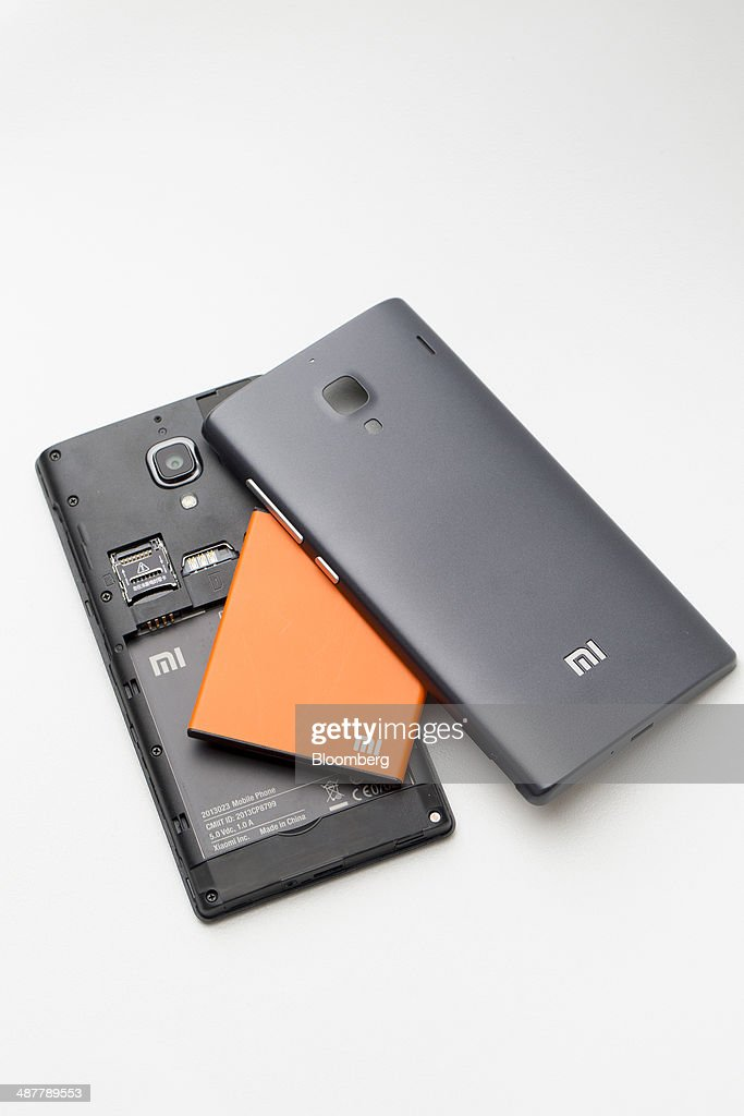 A Xiaomi Corp. Redmi smartphone battery is displayed between the phone's covers in an arranged photograph inside a 3 Hong Kong store, operated by Hutchison Whampoa Ltd., in Hong Kong, China, on Wednesday, April 30, 2014. Xiaomi, which sells more phones in China than Apple, is expanding to 10 more countries, including India and Brazil, after starting sales in Singapore earlier this year. Photographer: Brent Lewin/Bloomberg via Getty Images
