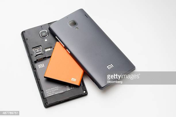 A Xiaomi Corp Redmi smartphone battery is displayed between the phone's covers in an arranged photograph inside a 3 Hong Kong store operated by...