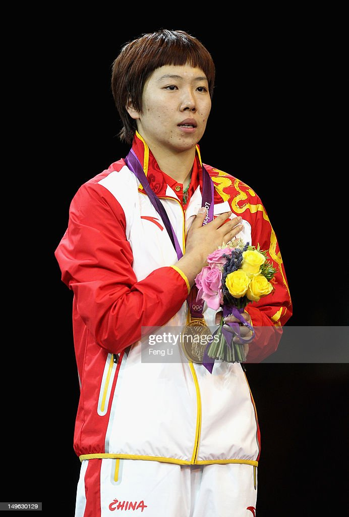 <a gi-track='captionPersonalityLinkClicked' href=/galleries/search?phrase=Xiaoxia+Li&family=editorial&specificpeople=4049514 ng-click='$event.stopPropagation()'>Xiaoxia Li</a> of China stands on the podium for her national anthem after winning the Gold medal in the Women's Singles Table Tennis Gold Medal match against Ning Ding of China on Day 5 of the London 2012 Olympic Games at ExCeL on August 1, 2012 in London, England.