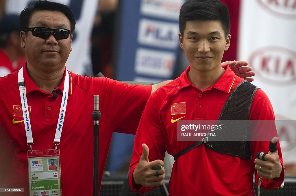 Xiaoxiang Dai of China (R) celebrates next to his coach with his gold medal after the Archery World Cup recurve men individual final competition against Jeff Henckels of Luxembourg in Medellin, Antioquia department, Colombia on July 21, 2013. AFP PHOTO/Raul ARBOLEDA