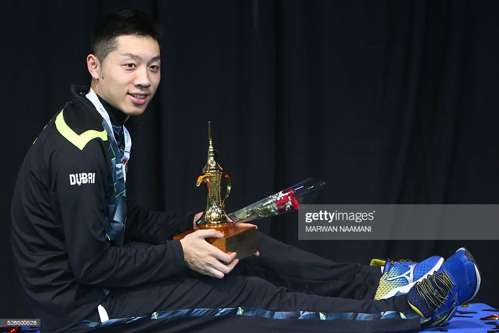 Xin Xu of China poses with his trophy after winning the men's single final match in the ITTF Nakheel Table Tennis Asian Cup, on April 30, 2016 in Dubai. / AFP / MARWAN