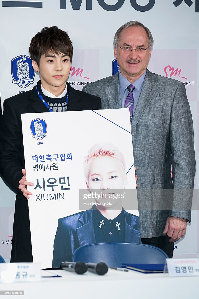 Xiumin of boy band <a gi-track='captionPersonalityLinkClicked' href=/galleries/search?phrase=EXO+-+Band&family=editorial&specificpeople=9756418 ng-click='$event.stopPropagation()'>EXO</a> and South Korean team head coach <a gi-track='captionPersonalityLinkClicked' href=/galleries/search?phrase=Uli+Stielike&family=editorial&specificpeople=746980 ng-click='$event.stopPropagation()'>Uli Stielike</a> pose for a picture after signing a Memorandum of Understanding (MoU) between Korea Football Association and SM Entertainment at Korea Football Association on December 11, 2014 in Seoul, South Korea. The MoU was designated for diversifying Korean soccer and K-wave through mutual exchange of sports and entertainment business industry.