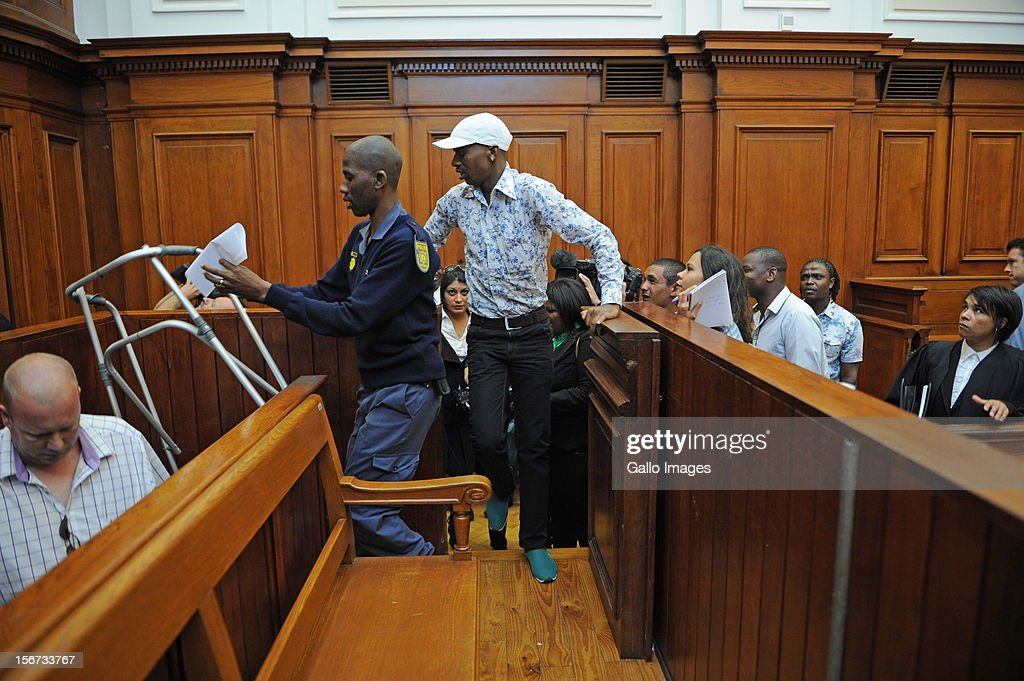 Xolile Mngeni is assisted by a police officer in the Cape Town High Court on November19, 2012 in Cape Town, South Africa. Mngeni was found guilty of robbery with aggravating circumstances, premeditated murder and illegal possession of a firearm and ammunition, after his involvement with the murder of Anni Dewani, allegedly plotted by her British husband Shrien Dewani.