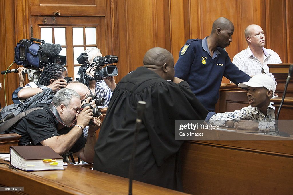 Xolile Mngeni is surrounded by photographers in the Cape Town High Court on November19, 2012 in Cape Town, South Africa. Mngeni was found guilty of robbery with aggravating circumstances, premeditated murder and illegal possession of a firearm and ammunition, after his involvement with the murder of Anni Dewani, allegedly plotted by her British husband Shrien Dewani.