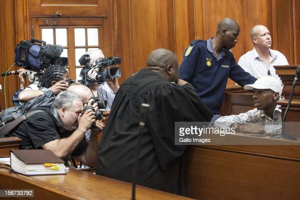 Xolile Mngeni is surrounded by photographers in the Cape Town High Court on November19 2012 in Cape Town South Africa Mngeni was found guilty of...