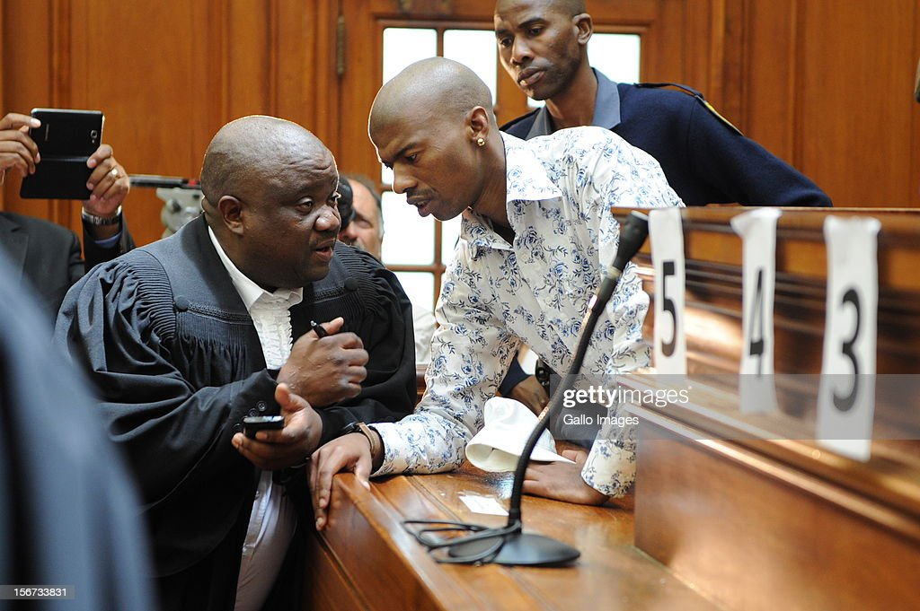 Xolile Mngeni speaks to his lawyer in the Cape Town High Court on November19, 2012 in Cape Town, South Africa. Mngeni was found guilty of robbery with aggravating circumstances, premeditated murder and illegal possession of a firearm and ammunition, after his involvement with the murder of Anni Dewani, allegedly plotted by her British husband Shrien Dewani.