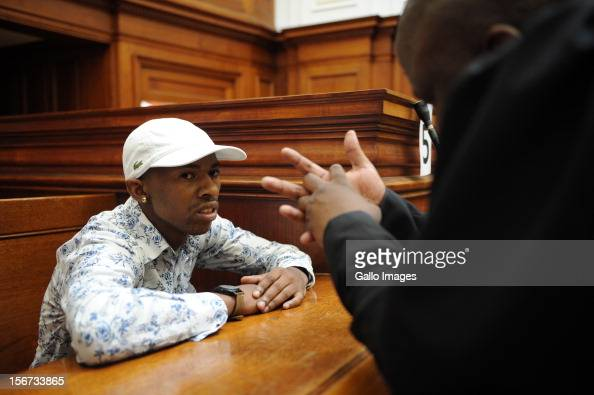 Xolile Mngeni speaks to his lawyer in the Cape Town High Court on November19 2012 in Cape Town South Africa Mngeni was found guilty of robbery with...