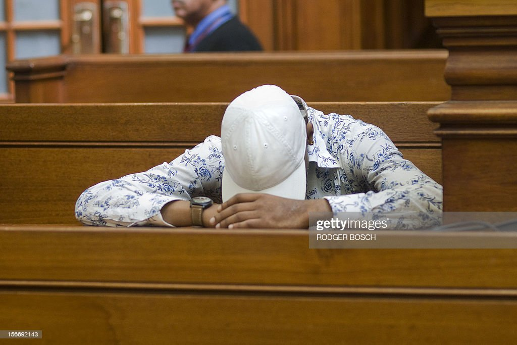 Xolile Mngeni (L), the man accused of killing Swedish honeymooner Anni Dewani, waits at Cape Town's High Court on November 19, 2012, before hearing his judgment. Mngeni claimed innocence in the November 2010 killing but admitted to his palm print having been found on the car in which Dewani's lifeless body was found in a poor Cape Town township. State prosecutor told Mngeni that his claims of not being at the murder scene were lies, as witnesses had testified otherwise and claimed that he had pulled the trigger. The 25-year-old had also been found in possession of items taken from Dewani and the honeymooning couple's taxi driver and had pointed out key details of the slaying to police after his arrest, prosecutor said. AFP PHOTO / RODGER BOSCH