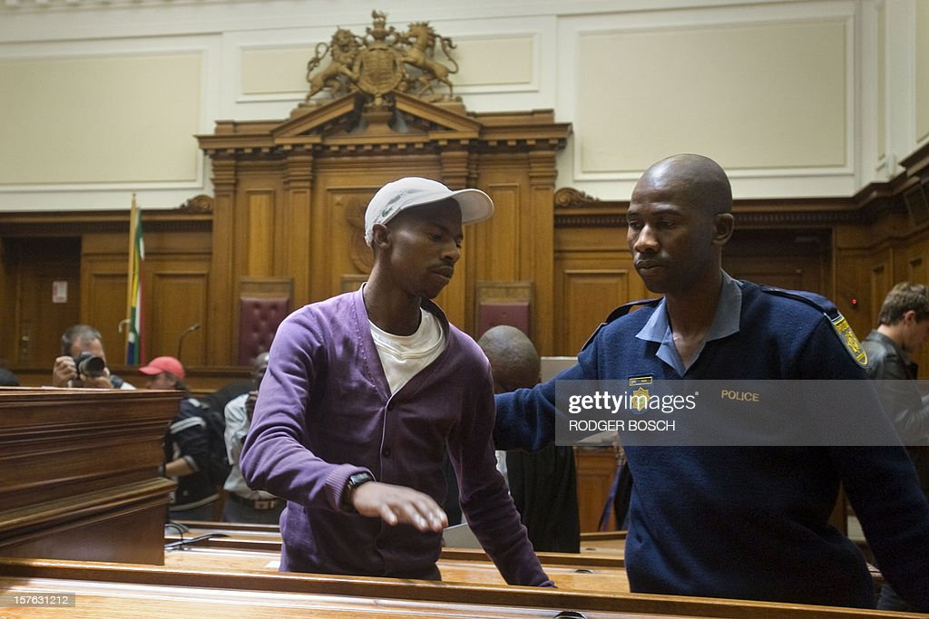 Xolile Mngeni, the man convicted of firing the bullet that killed Swedish tourist, Anni Dewani, in a simulated hijacking in Khayelitsha in 2011 is helped out of his seat in the High Court of Cape Town on December 5, 2012 for the final sentencing. Mngeni has been sentenced to life imprisonment on the charges of murder, robbery and illegal possession of a firearm and ammunition in the Cape High Court after being cleared as fit to stand trial despite his brain tumour. Dewani's husband, Shrien is fighting against being extradited from the UK to South Africa, allegedly for masterminding his wife's murder on November 13, 2011 in a poor township on the outskirts of Cape Town. AFP PHOTO / RODGER BOSCH