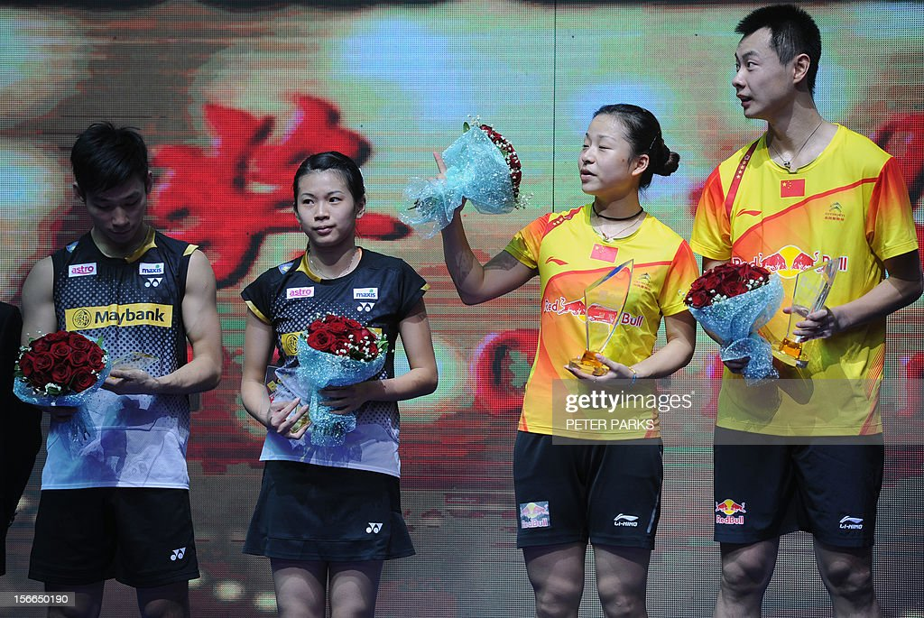 Xu Chen (R) and Ma Jin (2nd R) of China hold bunches of flowers as they celebrate beating Peng Soon Chan (L) and Liu Ying Goh (2nd L) of Malaysia in the mixed doubles final at the China Open badminton tournament in Shanghai on November 18, 2012. AFP PHOTO/Peter PARKS